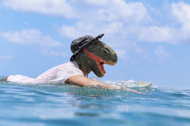 Man wearing dinosaur mask swimming with surfboard in sea