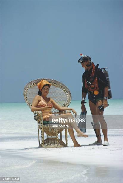 A man wearing diving equipment talks with a girl in a wicker chair on the beach Bahamas 1967