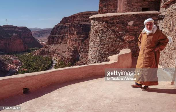 man wearing djellaba in fortified granary agadir id aissa, amtoudi, morocco, africa - agadir stock pictures, royalty-free photos & images