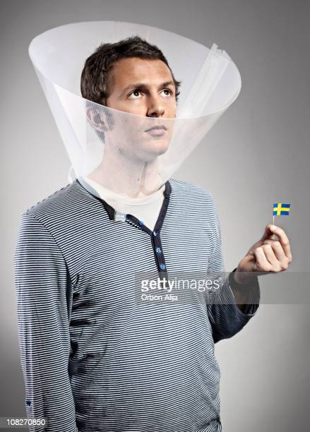 man wearing dog cone holding mini swedish flag - elizabethan collar stock photos and pictures