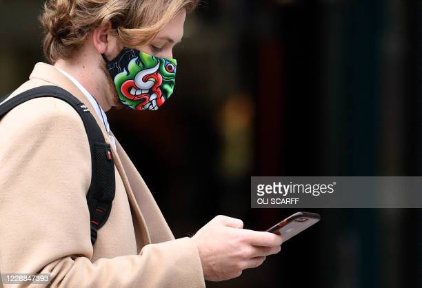 Man wearing dragon-themed face mask or covering due to the COVID-19 pandemic, uses an Apple iPhone in Liverpool, north west England on October 2...