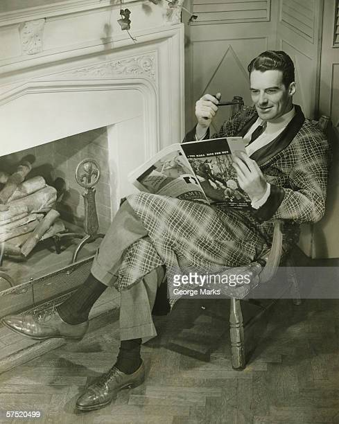 Man wearing, dressing gown reading magazine in front of fireplace, (B&W)