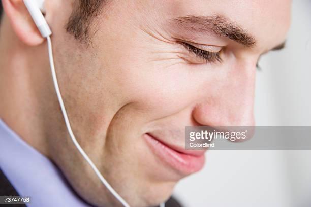 Man wearing earphones, smiling, close-up