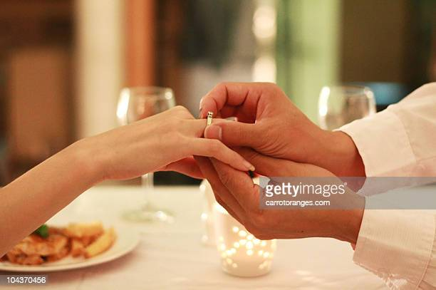 man wearing engagement ring to woman hand - man holding engagement ring stock photos and pictures