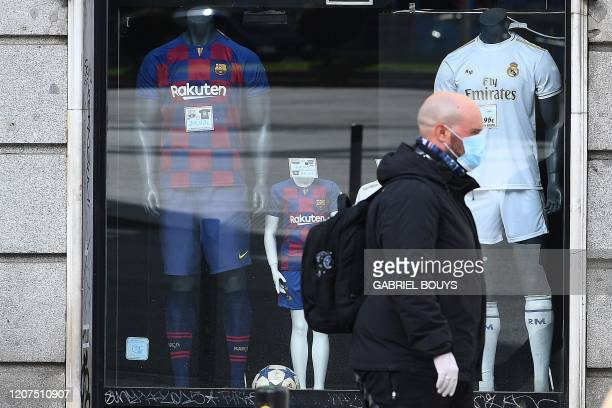 A man wearing face mask and gloves as a protective measure walks past a sporting ware shop displaying Real Madrid and FC Barcelona football teams'...