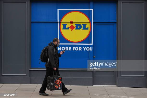 Man wearing face mask walks by Lidl store in Dublin city center during Level 5 Covid-19 lockdown. On Friday, 15 January in Dublin, Ireland.