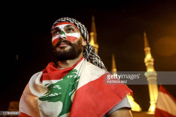 Man wearing facepaint in the colours of the Lebanese national flag and draped in a flag attends a demonstration at the Martyrs' Square in the centre...
