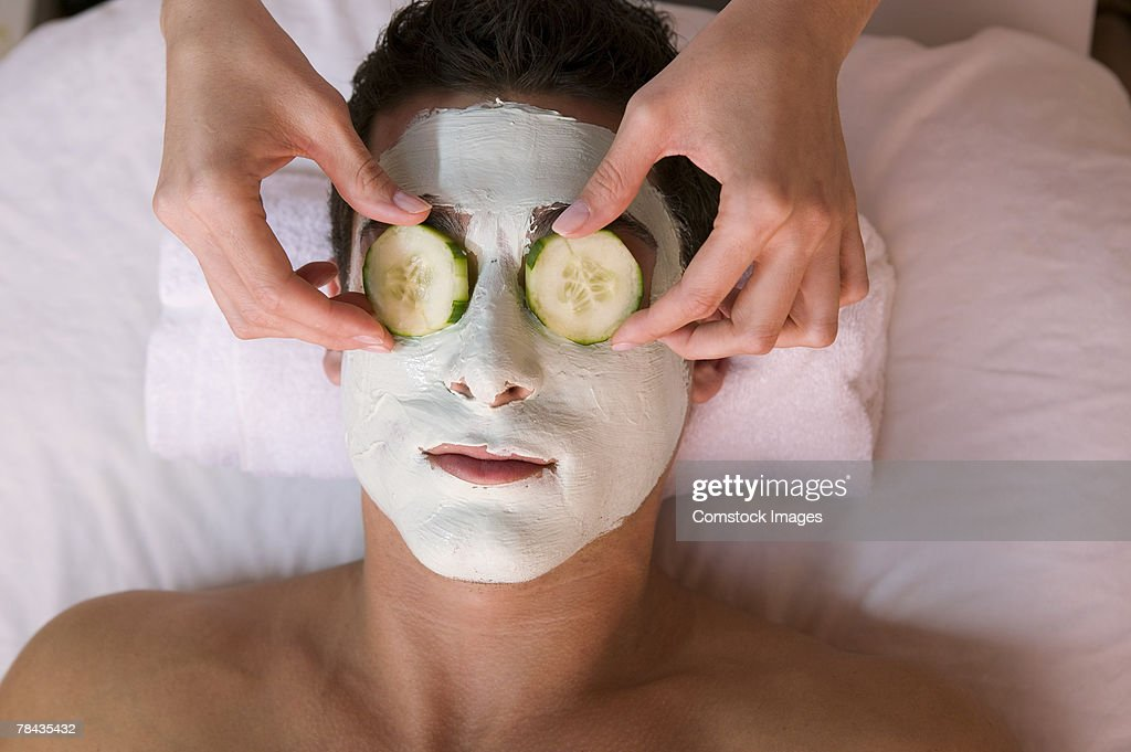 Man wearing facial mask and cucumber slices : Stockfoto