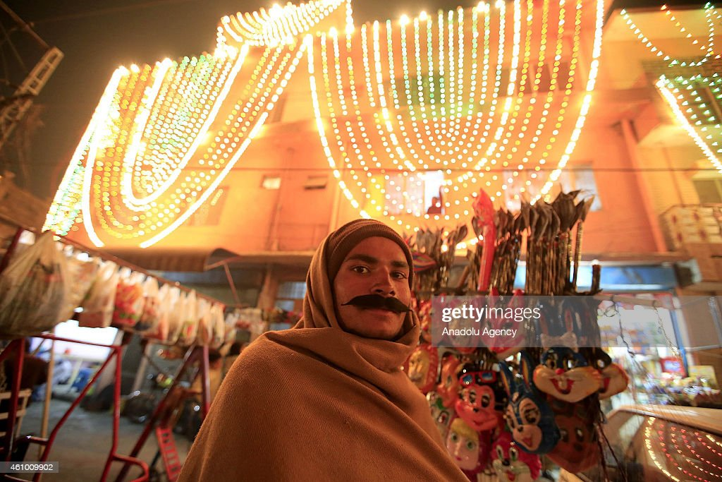 A man wearing false beard is seen as streets and buildings are decorated with lights and ornaments within the ceremony marking the 1444th anniversary of the birthday of Prophet Mohammad, Mawlid al Nabi, in Rawalpindi, Pakistan on January 3, 2015.