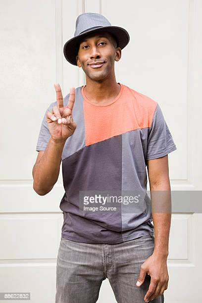 Man wearing fedora and doing peace sign
