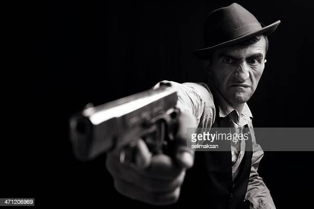 Man wearing fedora hat aiming gun with a furious face