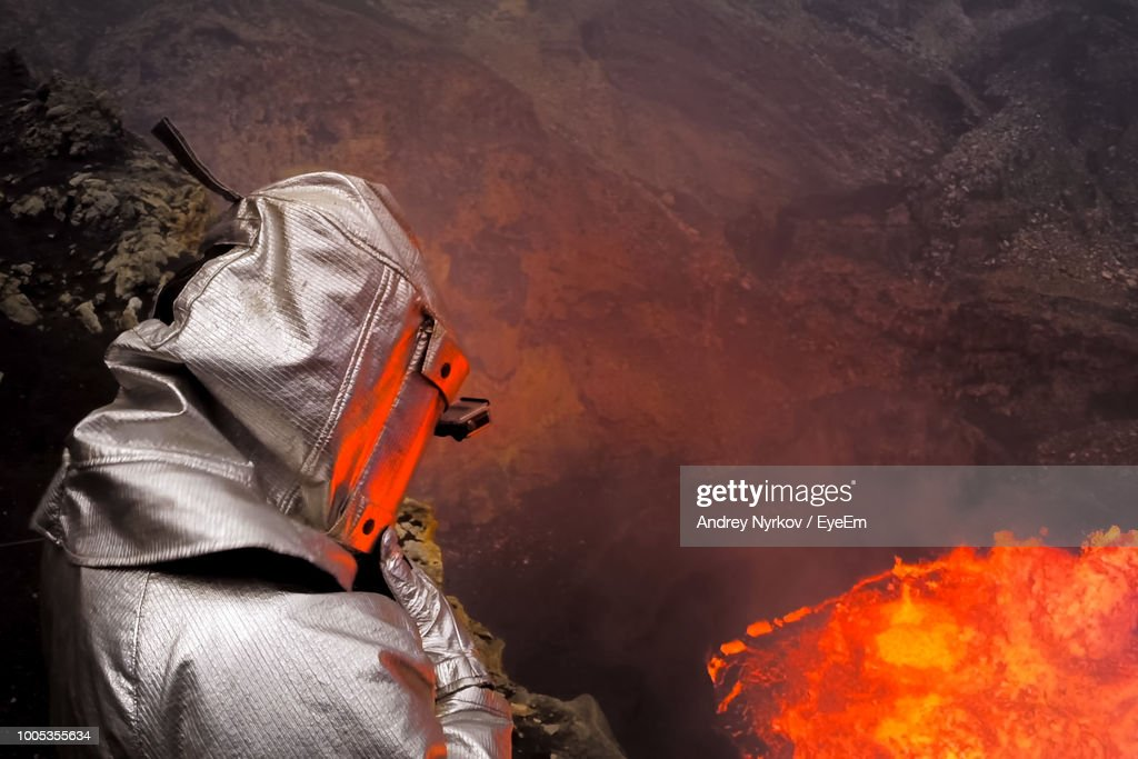 Man Wearing Fire Protection Suit While Standing Against Lava : Foto de stock