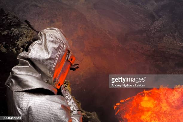 man wearing fire protection suit while standing against lava - fire protection suit stock photos and pictures
