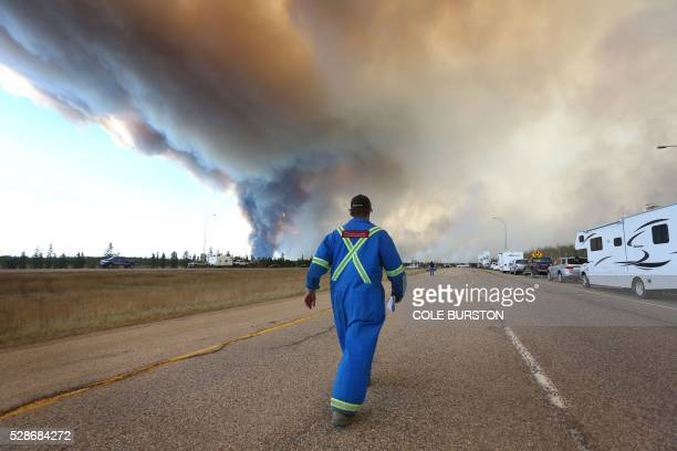 A man wearing fire retardant clothing walks up to a road block on Highway 63 as smoke rises from a forest fire near Fort McMurray Alberta on May 6...
