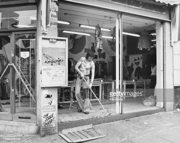 Man wearing flared jeans and a t-shirt uses a broom to sweep up the broken glass from the shattered windows of the 'Nothing to Hide' clothes shop on...