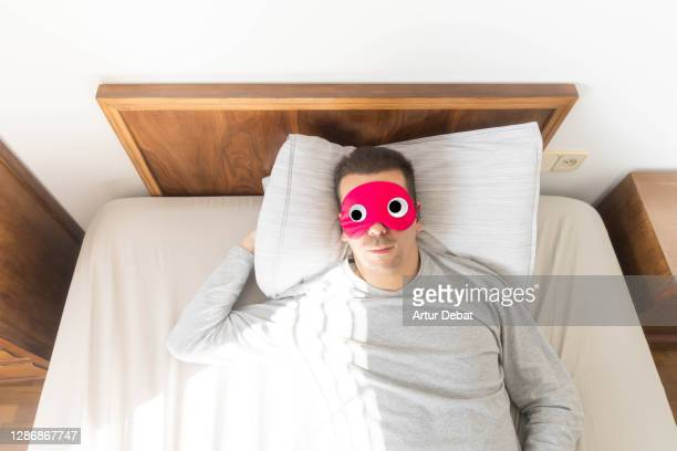 man wearing funny sleep mask with googly eyes resting in bed during morning. - april fools day stock pictures, royalty-free photos & images
