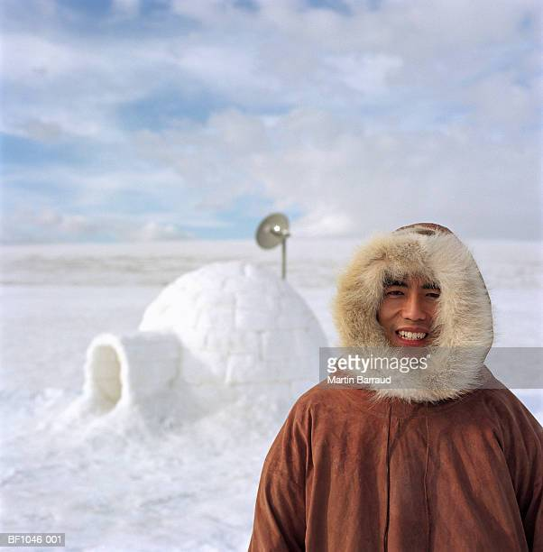 Man wearing fur-lined hood, igloo in background, portrait