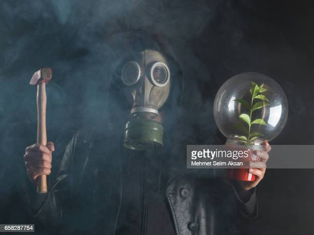 Man Wearing Gas Mask Under Smoke Holding Hammer And Plant In Bell Jar