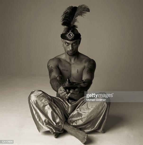 Man wearing genie outfit sitting on floor, holding lamp (Toned B&W)