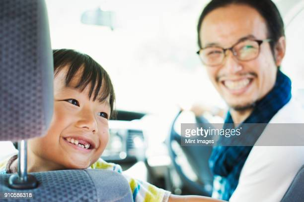 Man wearing glasses and boy sitting in a car, smiling at camera.