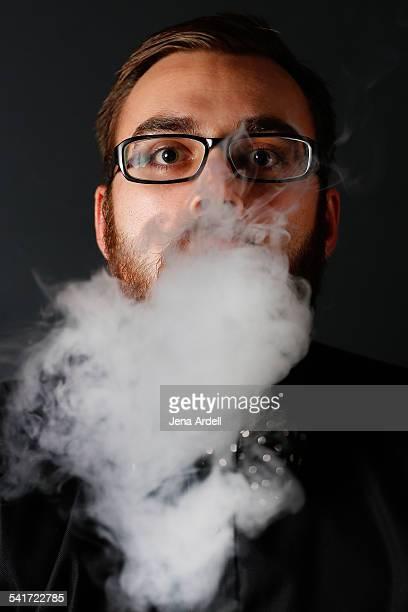 Man Wearing Glasses Blowing Smoke Toward Camera