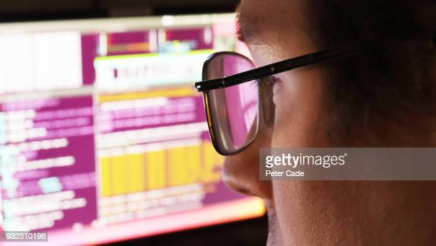 man wearing glasses looking at computer screen - programmer stock pictures, royalty-free photos & images