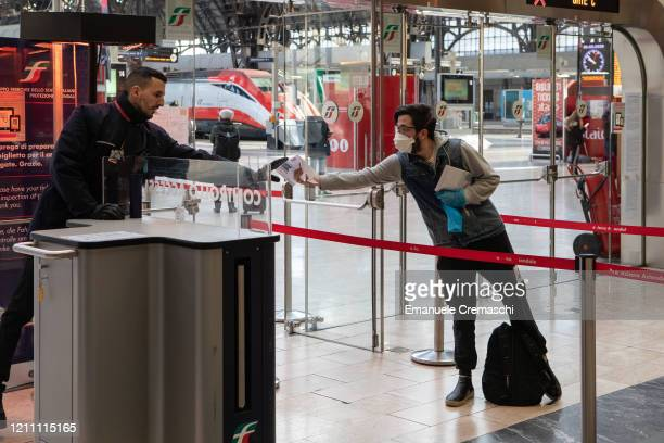 A man wearing gloves and a face mask shows his ticket to a steward as he goes through security control at Milan's Central Station on March 08 2020 in...