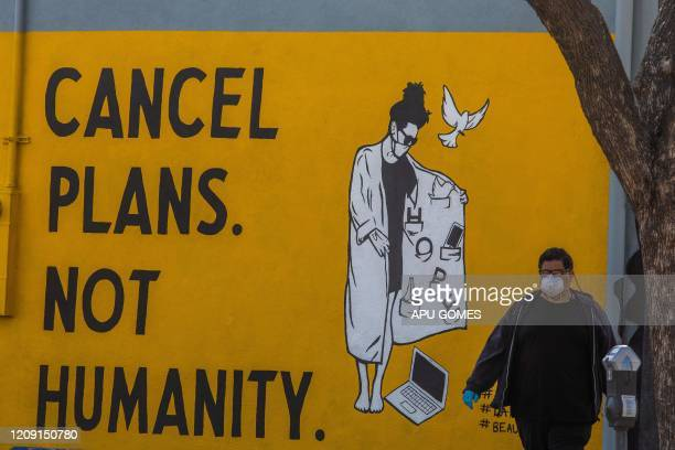 A man wearing gloves and a face mask walks by a mural reading Cancel Plans Not Humanity during the coronavirus pandemic on April 4 2020 in Los...