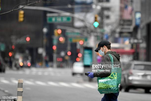A man wearing gloves and a protective mask carrying a Whole Foods shopping bag walks across an empty intersection at 56th Street and Broadway amid...