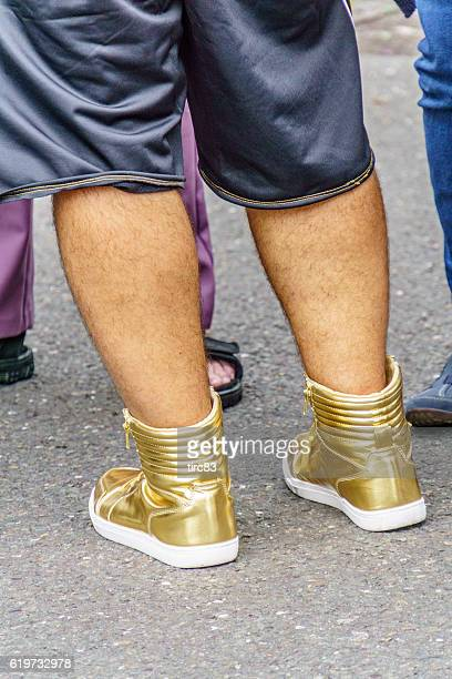 man wearing gold boots - men with hairy legs stock photos and pictures