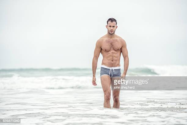 Man wearing grey swim shorts in the sea.