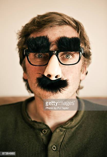 man wearing grouch marx glasses and nose - groucho marx stock photos and pictures