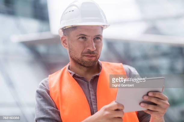 man wearing hard hat and high viz using digital tablet - sigrid gombert stock-fotos und bilder