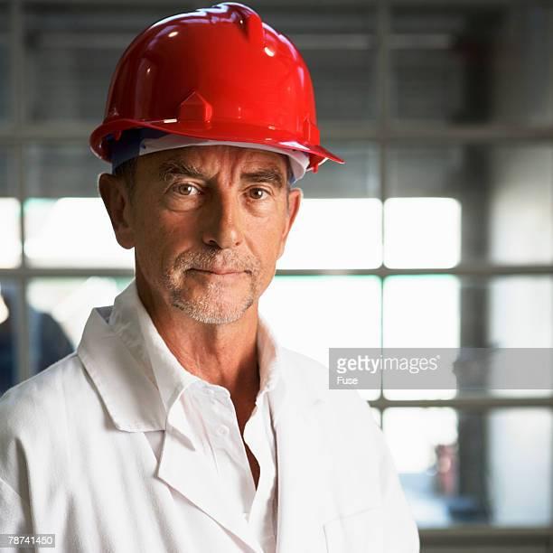 Man Wearing Hard Hat and Lab Coat
