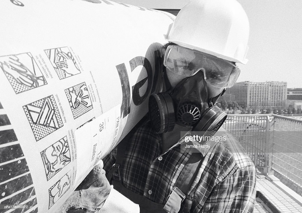 Man wearing hard hat, pollution mask and glasses, carrying roll of insulation on shoulder, close-up, b&w : Stockfoto