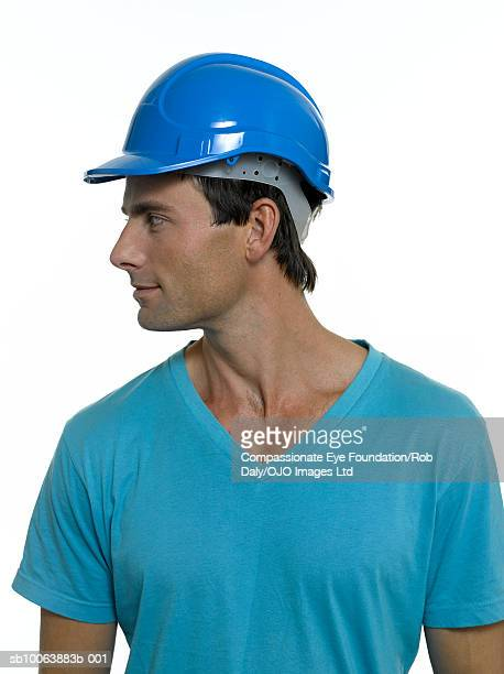 Man wearing hard hat, turning to side