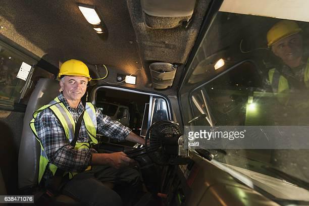Man wearing hardhat driving truck