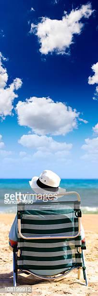 uomo con cappello seduto su una sedia sulla spiaggia - solo un uomo foto e immagini stock