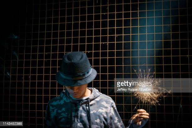 man wearing hat holding illuminated sparkler against fence - jeffrey roque stock photos and pictures
