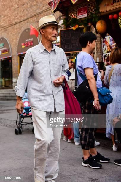 man wearing hat in urumqi, xinjiang - sergio amiti stock pictures, royalty-free photos & images