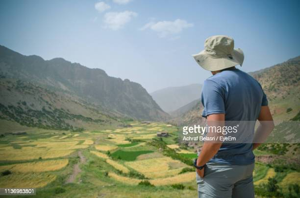 Man Wearing Hat Looking At Mountain Range Against Sky