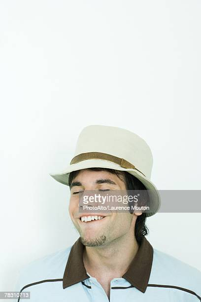 Man wearing hat, making faces, eyes closed