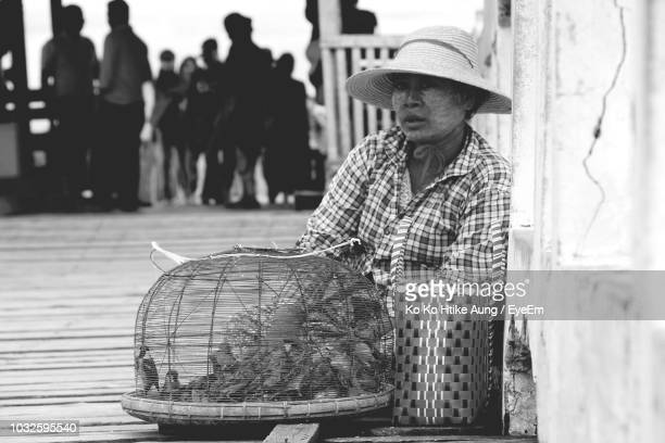 man wearing hat selling birds by road - ko ko htike aung stock pictures, royalty-free photos & images