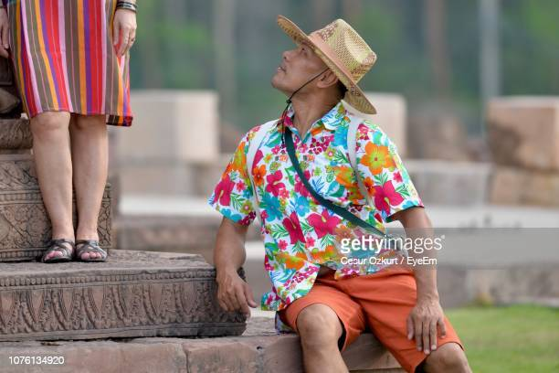 man wearing hat while sitting on steps - only mid adult men stock pictures, royalty-free photos & images