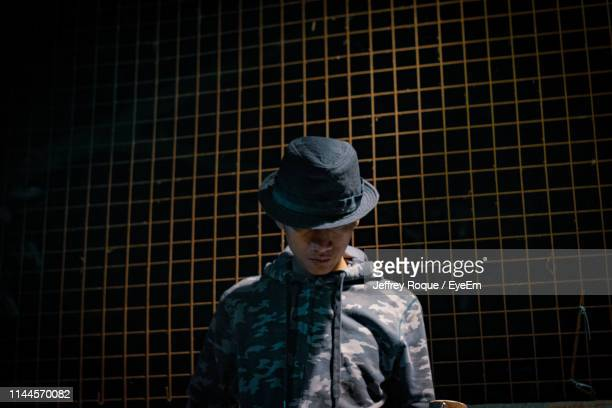 man wearing hat while standing against fence - jeffrey roque stock photos and pictures