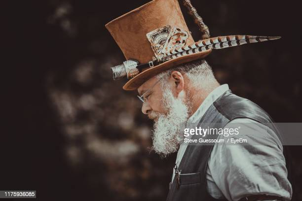 man wearing hat while standing outdoors - steve guessoum stockfoto's en -beelden