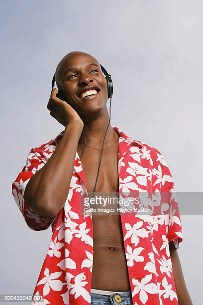 man wearing hawaiian shirt and headphones, smiling, low angle view - 前をはだけた ストックフォトと画像