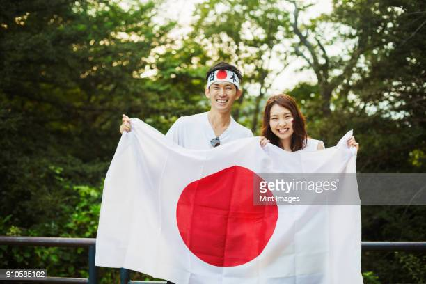 man wearing headband and young woman with brown hair and face paint holding japanese flag, smiling at camera. - japanese flag stock photos and pictures
