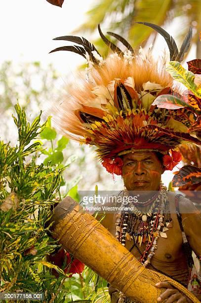 Man wearing headdress, holding drum, portrait