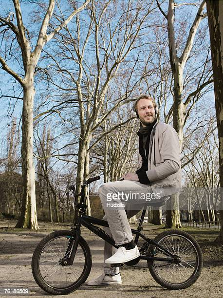 A man wearing headphones and sitting on a BMX in a park